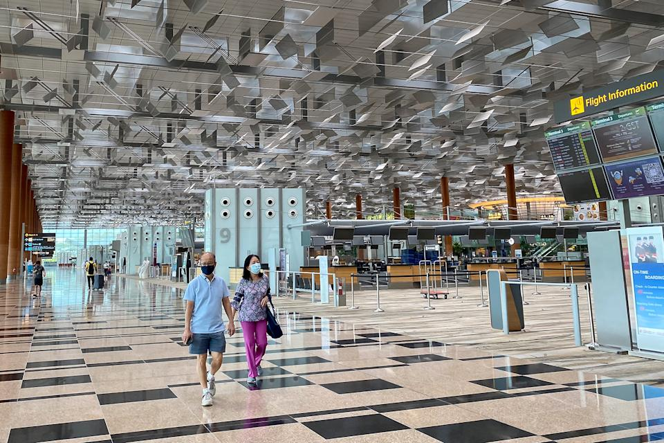 A couple seen walking past the empty check-in rows at Changi Airport's Terminal 3 on 11 October 2020. (PHOTO: Dhany Osman / Yahoo News Singapore)