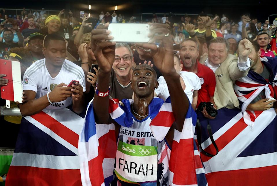 <p>Mohamed Farah of Great Britain takes a photo after winning gold in the Men's 5000 meter Final on Day 15 of the Rio 2016 Olympic Games at the Olympic Stadium on August 20, 2016 in Rio de Janeiro, Brazil. (Photo by Patrick Smith/Getty Images) </p>