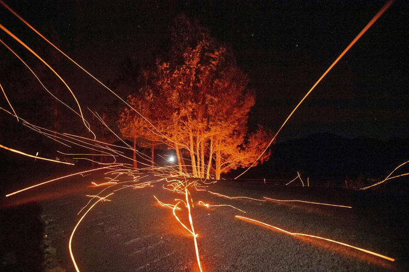FILE - In this Oct. 29, 2019, file photo, strong winds send embers flying across Ida Clayton Road as the Kincade Fire burns in Calistoga, Calif. The Sonoma County Board of Supervisors voted Tuesday, Jan. 14, 2020, to hire two law firms to pursue legal action against Pacific Gas & Electric, the nation's largest utility. The action comes as PG&E is trying to dig out of a financial hole created by a series of catastrophic fires that have been blamed on the utility's outdated electrical system and managerial negligence (AP Photo/Noah Berger, File)