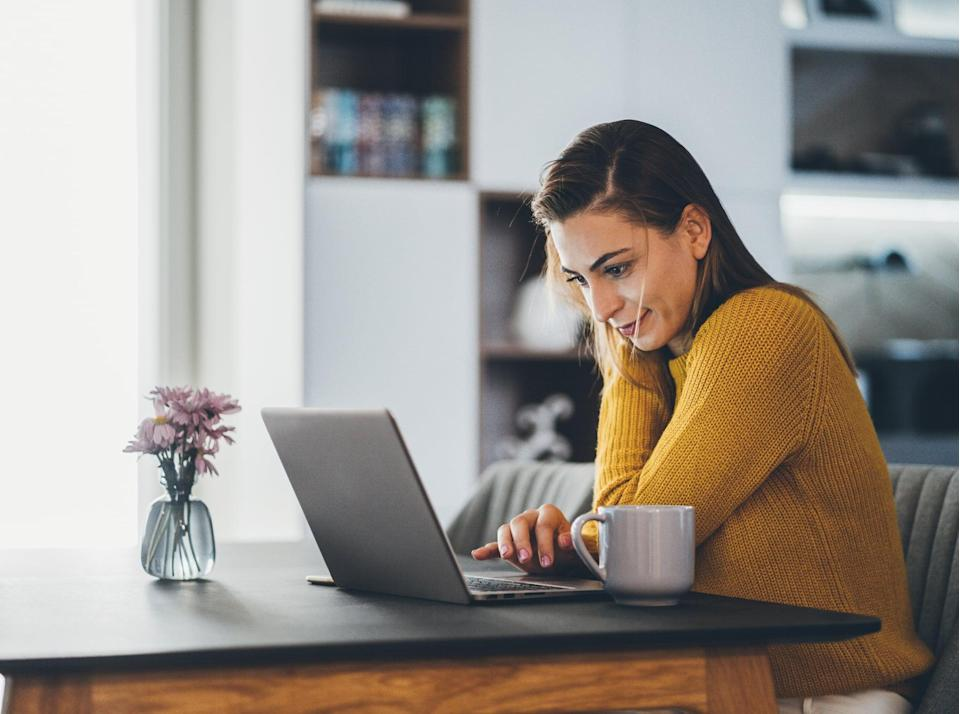Young woman working at home, typing on laptop