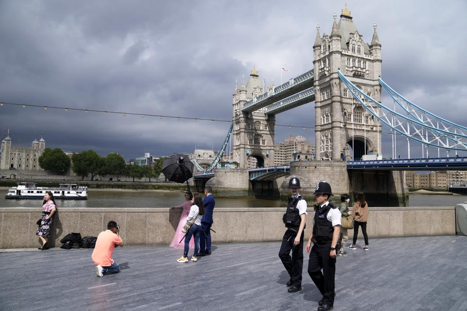 FILE - In this July 3, 2021, file photo, policemen patrol near Tower Bridge as a bride is photographed on the bank of Thames river in London. Britain's Conservative government is hoping a combination of relatively high vaccination rates and common-sense behavior will keep a lid on coronavirus infections this fall and winter and avoid the need for restrictive measures. (AP Photo/Thanassis Stavrakis, File)