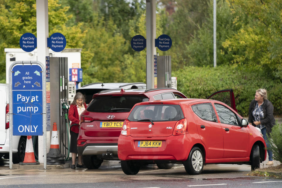 Members of the public are seen at a petrol station in Manchester, England, Monday, Sept. 27, 2021. British Prime Minister Boris Johnson is said to be considering whether to call in the army to deliver fuel to petrol stations as pumps ran dry after days of panic buying. ( AP Photo/Jon Super)