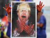 FILE - In this Aug. 26, 2020 file photo a nurse holds a painting of Prime Minister Boris Johnson clapping with blood on his hands as part of a demonstration of NHS workers at hospitals across London to demand a 15 per cent pay rise by the government in London.(AP Photo/Kirsty Wigglesworth, File)