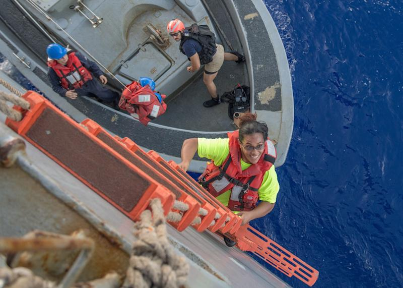 Tasha Fuiava, an American who had been sailing for five months on a damaged sailboat, climbs the ladder to board the amphibious dock landing ship USS Ashland.
