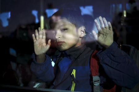 A migrant boy is seen through a bus window following his arrival by the Blue Star Patmos passenger ferry from the island of Lesbos at the port of Piraeus