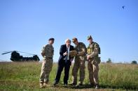 Britain's Prime Minister Boris Johnson flies a Black Hornet nano drone during a meeting with military personnel on Salisbury plain training area near Salisbury