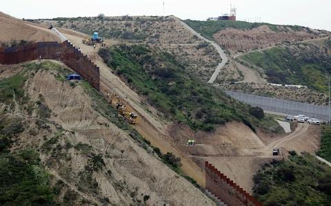 Construction crews replace a section of the primary wall separating San Diego, above right, and Tijuana, Mexico - Credit: Gregory Bull/AP