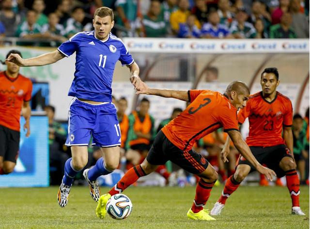 Bosnia-Herzegovina forward Edin Dzeko (11) vies for the ball against Mexico defender Carlos Salcido (3) during the first half of an international friendly soccer match at Soldier Field in Chicago, Tuesday, June 3, 2014. (AP Photo/Kamil Krzaczynski)