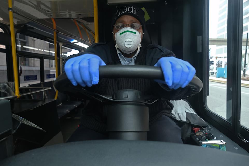 A bus driver for the Detroit, Michigan city bus line DDOT poses for a portrait wearing a protective mask and gloves for protection in Detroit, Michigan, on March 24, 2020, during the novel coronavirus (COVID-19) outbreak. - At 12:01 am Tuesday March 24,2020 Governor Gretchen Whitmer ordered a 'Stay at Home and Stay Safe Order' to slow the spread of Coronavirus (COVID-19) across the State of Michigan which now has 1,791 confirmed cases and 24 deaths due to the virus. (Photo by SETH HERALD / AFP) (Photo by SETH HERALD/AFP via Getty Images)