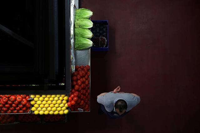 <p>A grocer waits for customers next to his stand at a food market in Madrid, Spain, May 17, 2017. (Photo: Susana Vera/Reuters) </p>