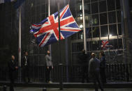 FILE - In this Friday, Jan. 31, 2020 file photo the Union flag is lowered and removed from outside of the European Parliament in Brussels. Britain and the European Union have struck a provisional free-trade agreement that should avert New Year's chaos for cross-border commerce and bring a measure of certainty to businesses after years of Brexit turmoil. The breakthrough on Thursday, Dec. 24, 2020 came after months of tense and often testy negotiations that whittled differences down to three key issues: fair-competition rules, mechanisms for resolving future disputes and fishing rights. (AP Photo/Francisco Seco, File)