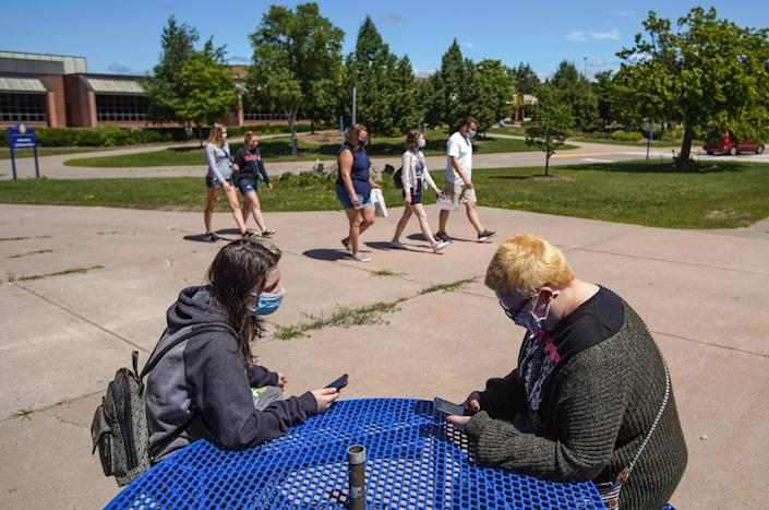 """Lake Superior State University freshman Taylor Owrutsky, left, of Round Lake, Ill., talks with junior Katherine Davis about theater club as students and family walk around campus during a move-in day for students on Aug. 5. """"I'm just cautious so I have a bunch of masks,"""" Owrutsky said."""