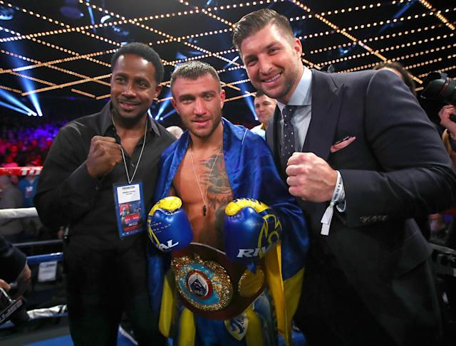 WBO junior lightweight champion Vasyl Lomachenko celebrates his sixth-round TKO victory over Guillermo Rigondeaux Saturday with former Heisman Trophy winners Desmond Howard (L) and Tim Tebow (R). (Mikey Williams/Top Rank)