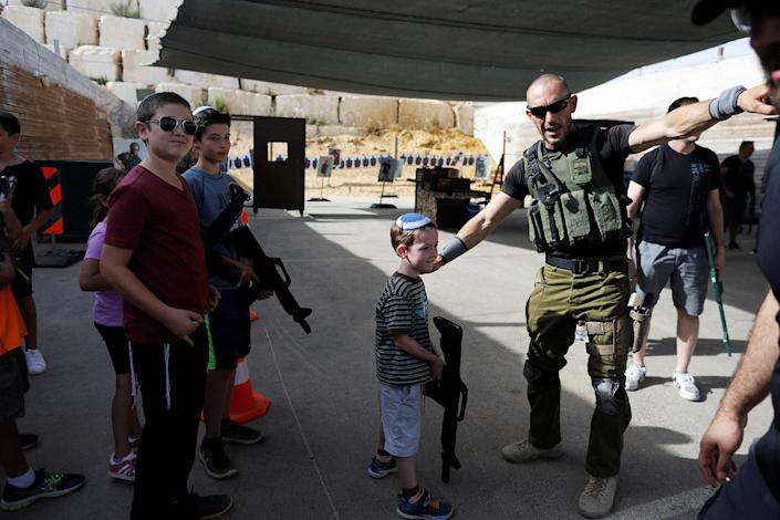 "<p>An Israeli instructor speaks to children from overseas holding wooden cut-out rifles as they take part in a two hour ""boot camp"" experience, at ""Caliber 3 Israeli Counter Terror and Security Academy"" in the Gush Etzion settlement bloc south of Jerusalem in the occupied West Bank July 13, 2017. (Photo: Nir Elias/Reuters) </p>"