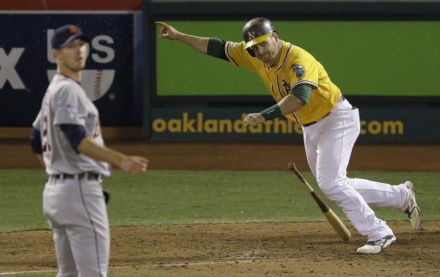 Oakland Athletics' Stephen Vogt, right, celebrates after hitting a single off of Detroit Tigers pitcher Rick Porcello, left, to score Yoenis Cespedes during the ninth inning of Game 2 of an American League Division Series in Oakland, Calif., Saturday, Oct. 5, 2013. The Athletics won 1-0. (AP Photo/Jeff Chiu)