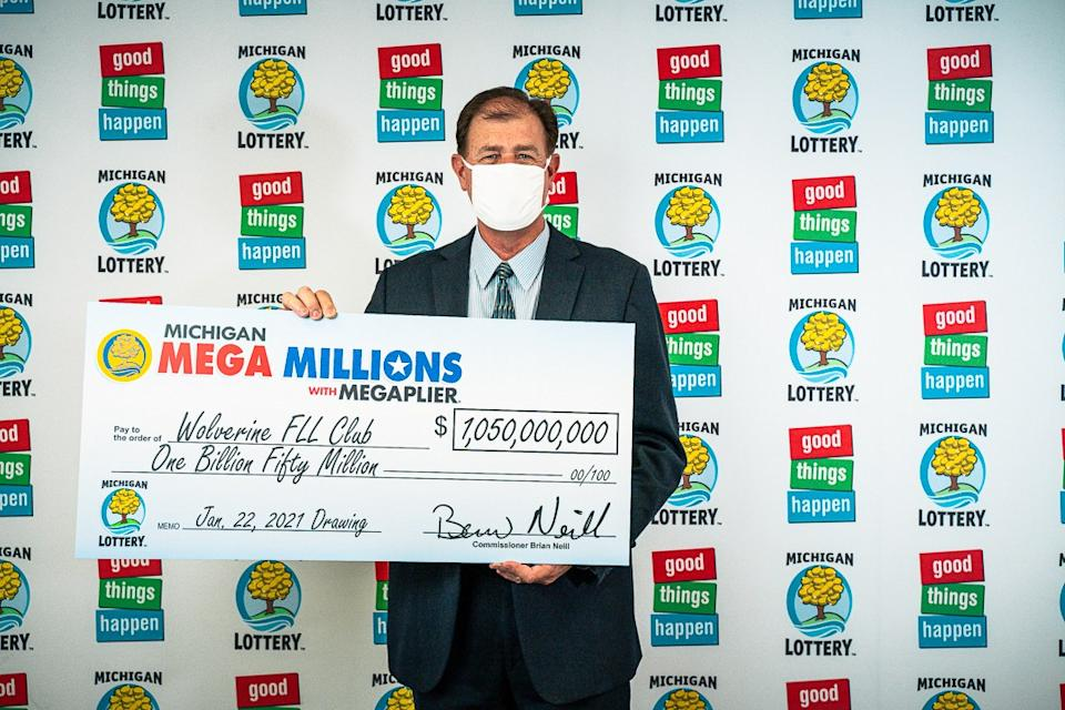 Attorney Kurt Panouses poses with a check on behalf of the winners of a Mega Millions lottery jackpot. Source: Michigan Lottery via AP