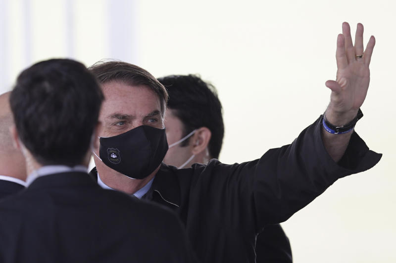 Brazil's President Jair Bolsonaro, wearing a face mask amid the new coronavirus pandemic, waves to supporters as he leaves the official residence of Alvorada palace, in Brasilia, Brazil, Monday, May 25, 2020. (AP Photo/Eraldo Peres)