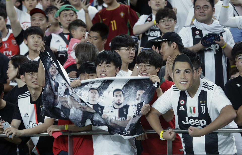 A South Korean soccer fans wears a mask of Cristiano Ronaldo of Juventus prior to a friendly match between Juventus and Team K League at the Seoul World Cup Stadium in Seoul, South Korea, Friday, July 26, 2019. (AP Photo/Ahn Young-joon)