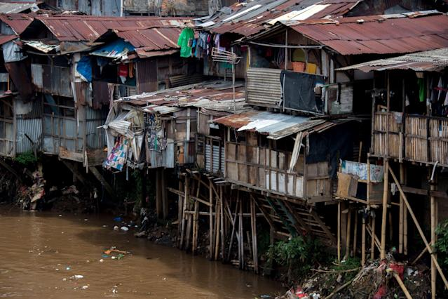 <p>Shanties with hanging toilets, and waste that runs straight into the river below, Jakarta, Indonesia. (Photo: Bay Ismoyo/AFP/Getty Images) </p>