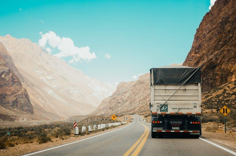 Truck driving along mountain road.