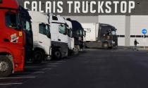 """A lorrie driver walks past trucks at """"Calais Truckstop"""" private parking in Marck"""