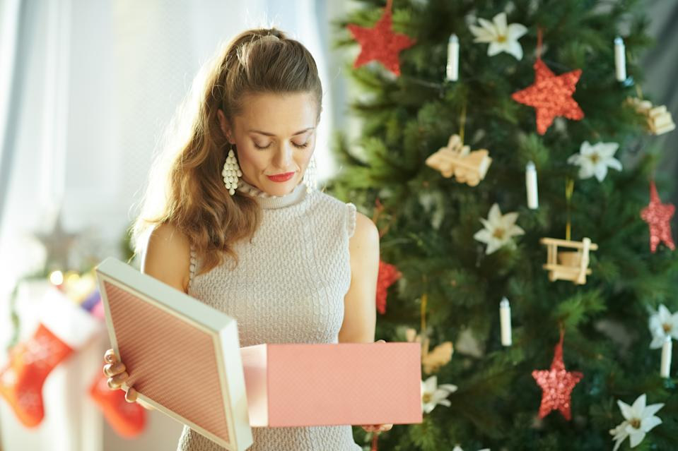 unhappy young woman with opened Christmas present box near Christmas tree