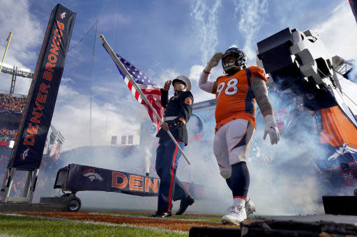 A Marine and Denver Broncos nose tackle Mike Purcell (98) salute as they take the field prior to an NFL football game against the Cleveland Browns Sunday, Nov. 3, 2019, in Denver. (AP Photo/Jack Dempsey)