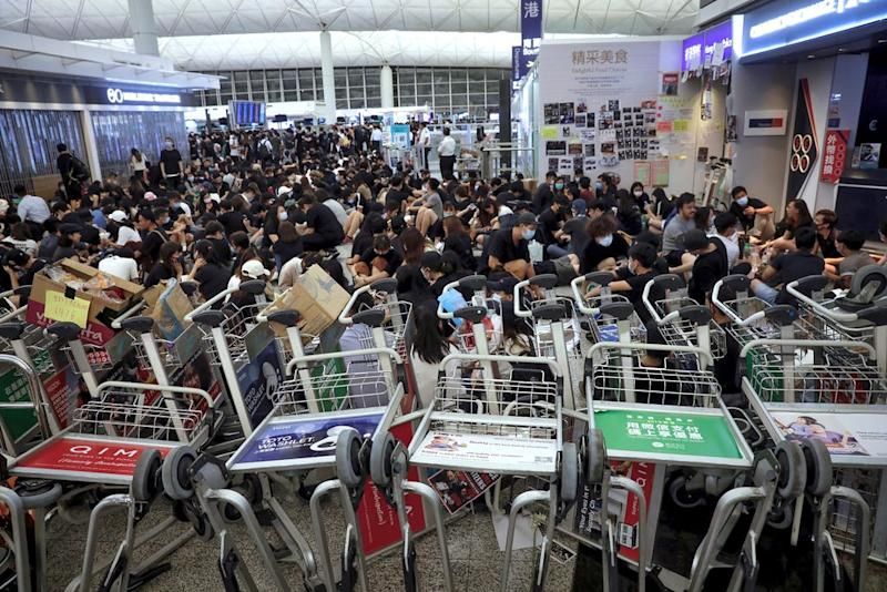 Protesters use luggage trolleys to block the walkway to the departure gates during a demonstration at the Airport in Hong Kong, Tuesday, Aug. 13, 2019. (AP Photo/Vincent Yu)