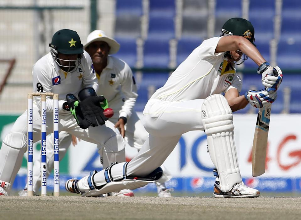 Pakistan's Safraz Ahmed (L) makes a catch to dismiss Australia's Nathan Lyon (R) during the fifth day of the second Test in Abu Dhabi on November 3, 2014 (AFP Photo/Karim Sahib)