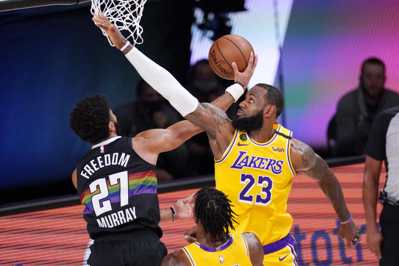 Denver Nuggets' Jamal Murray (27) scores past Los Angeles Lakers' LeBron James (23) during the first half of an NBA conference final playoff basketball game Thursday, Sept. 24, 2020, in Lake Buena Vista, Fla. (AP Photo/Mark J. Terrill)