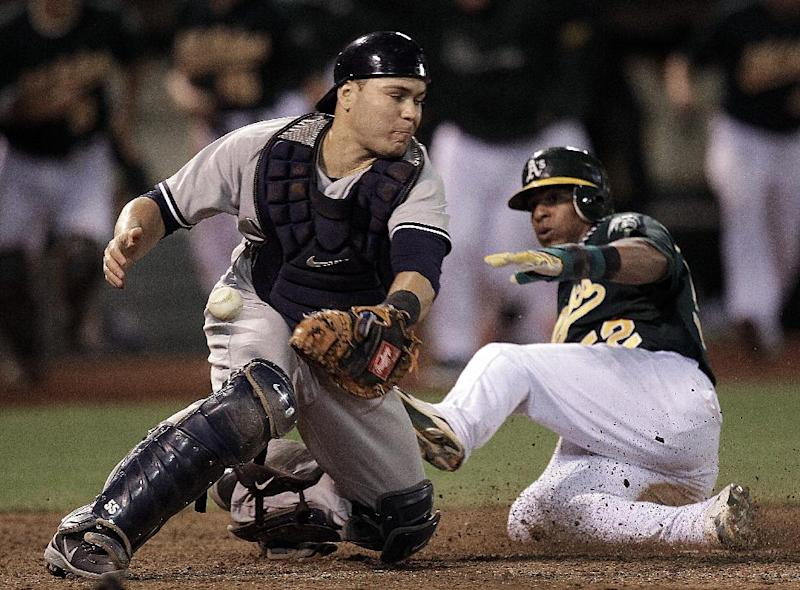 New York Yankees catcher Russell Martin, left, cant make the tag on Oakland Athletics' Yoenis Cespedes in the ninth inning of a baseball game Friday, July 20, 2012, in Oakland, Calif. Cespedes scored the winning run on a single hit by A's Brandon Moss. (AP Photo/Ben Margot)