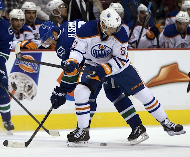 Vancouver Canucks' Henrik Sedin, left, of Sweden, and Edmonton Oilers' Ales Hemsky, of the Czech Republic, vie for the puck during the first period of a preseason NHL hockey game Wednesday, Sept. 18, 2013, in Vancouver, British Columbia. (AP Photo/The Canadian Press, Darryl Dyck)