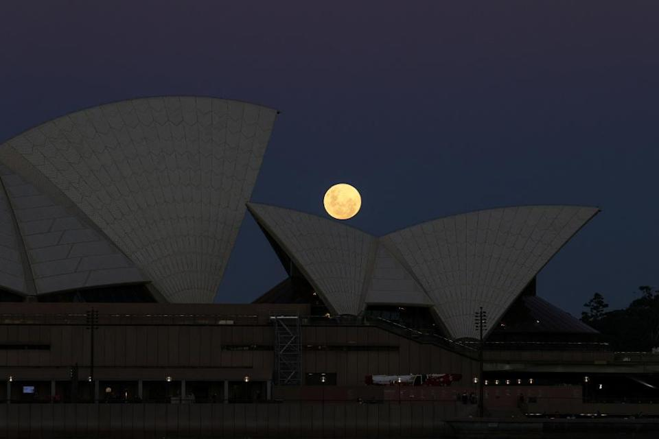 A Super Flower Moon rises behind the Sydney Opera House on the night of a lunar eclipse, in Sydney May 26, 2021. — Reuters pic