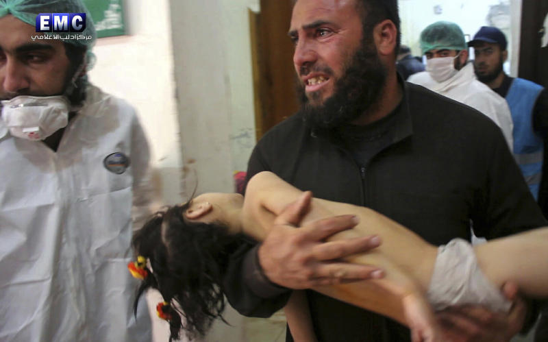 FILE -- This Tuesday April 4, 2017, file photo, provided by the Syrian anti-government activist group Edlib Media Center, that is consistent with independent AP reporting, shows a man carrying a child following a suspected chemical attack, at a makeshift hospital in the town of Khan Sheikhoun, northern Idlib province, Syria. Walid Moallem, Syria's Foreign Minister, told reporters Thursday, April 6, 2017, that it didn't use chemical weapons in Tuesday's attack, and he blamed the rebels for stockpiling the deadly substance. (Edlib Media Center, via AP, File)