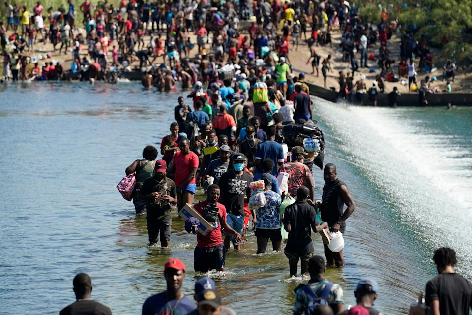 Haitian migrants use a dam to cross between the USA and Mexico on Sept. 17 in Del Rio, Texas. Thousands of Haitian migrants assembled under and around a bridge in Del Rio, presenting the Biden administration with another challenge as it tries to manage large numbers of asylum seekers reaching U.S. soil.