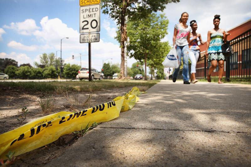 CHICAGO, IL - JULY 22: Crime scene tape lays along the sidewalk near where Maurice Gibson, 27, was shot and killed in front of Simeon Career Academy High School on July 22, 2013 in Chicago, Illinois. Gibson was klled on July 19 at the start of a violent weekend in Chicago which saw at least 6 people killed and 22 wounded by gun violence. (Photo by Scott Olson/Getty Images)