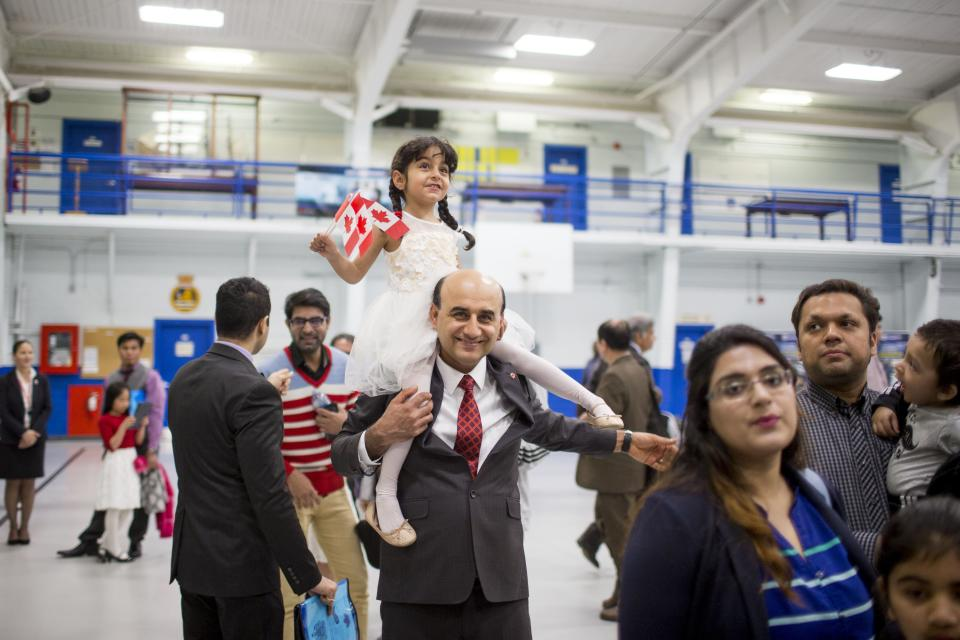 TORONTO, ON - MAY 2: Hadi Elhami, originally from Iran, carries his daughter, Arnika Elhami, on his shoulder during a citizenship ceremony held at the Royal Canadian Navy local reserve division HMCS York. 250 new Canadians took the oath on this day        (Carlos Osorio/Toronto Star via Getty Images)