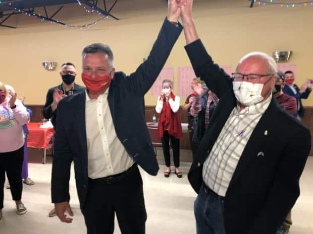Heath MacDonald, left, celebrates with Wayne Easter, the Liberal MP who had represented Malpeque since 1993. (Brian Higgins/CBC - image credit)