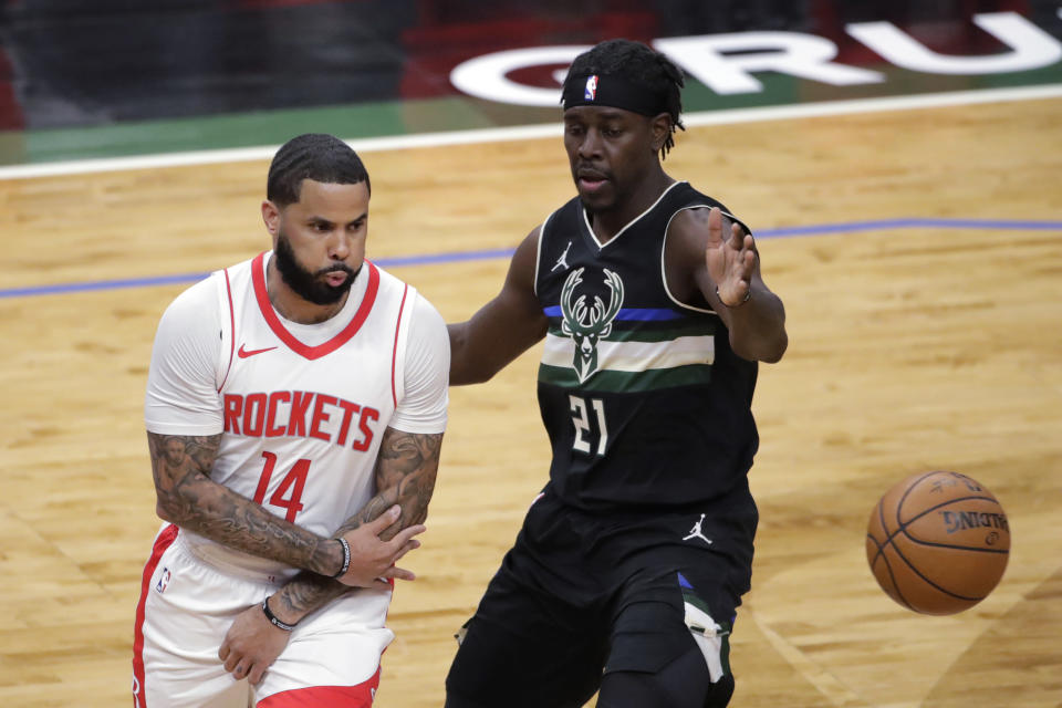 Houston Rockets' D.J. Augustin (14) passes the ball around Milwaukee Bucks' Jrue Holiday (21) during the first half of an NBA basketball game Friday, May 7, 2021, in Milwaukee. (AP Photo/Aaron Gash)