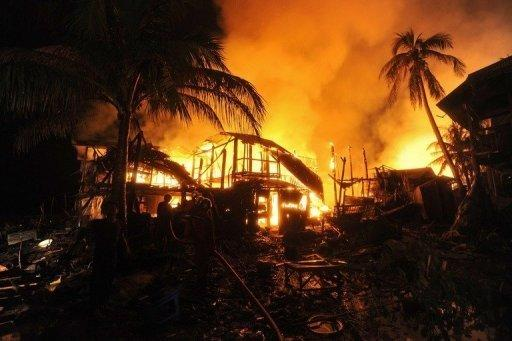 Firemen extinguish a fire engulfing houses in Sittwe, capital of the western state of Rakhine on June 15. Myanmar security forces opened fire on Rohingya Muslims, committed rape and stood by as rival mobs attacked each other during a recent wave of sectarian violence, a rights watchdog has said
