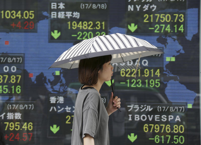 <p> A woman walks by an electronic stock board of a securities firm in Tokyo, Friday, Aug. 18, 2017. Asian stocks sank Friday as big losses on Wall Street amid continuing U.S. political turmoil and a deadly van attack in Spain pressured global investor sentiment. (AP Photo/Koji Sasahara) </p>