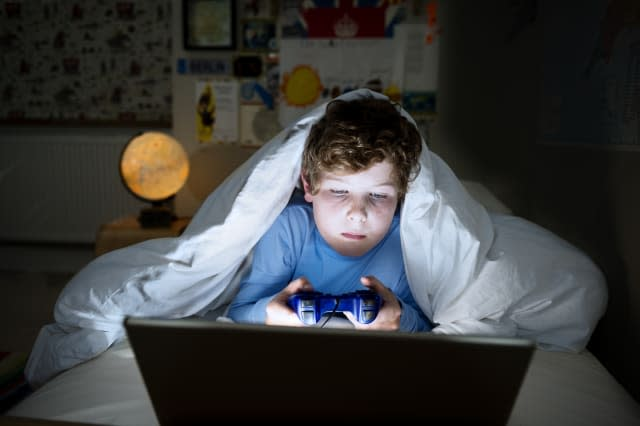 Young boy 10 years old playing on his computer late at night. Illustrating the idea that children are too tired for school in th