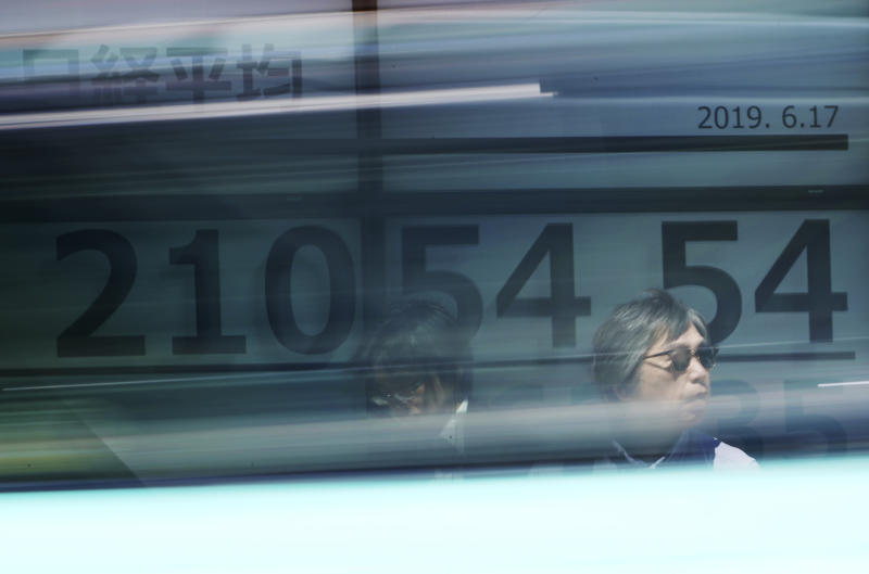Men stand in front of an electronic stock board showing Japan's Nikkei 225 index at a securities firm in Tokyo Monday, June 17, 2019. Asian shares were mostly higher Monday amid a wait-and-see attitude about the direction of interest rates and the trade dispute between the U.S. and China. (AP Photo/Eugene Hoshiko)