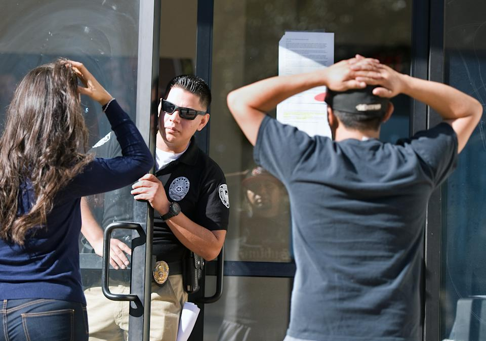 SANTA ANA, CA - APRIL 27: A security guard inside Everest College keeps away a member of the media and a former student Gary Montano after the embattled for-profit Santa Ana school was shut down along with 28 others on Monday. Montano, 30 who graduated two years ago, was trying to collect his transcripts and diploma.