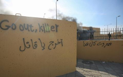 Graffiti left by protesters outside the US embassy - Credit: AHMAD AL-RUBAYE/AFP via Getty Image