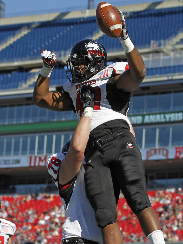Northern Illinois offensive linesman Ryan Brown (78) celebrates a touchdown by running back Cameron Stingily (42) during the first half of an NCAA football game against Massachusetts in Foxborough, Mass., Saturday, Nov. 2, 2013. (AP Photo/Stew Milne)