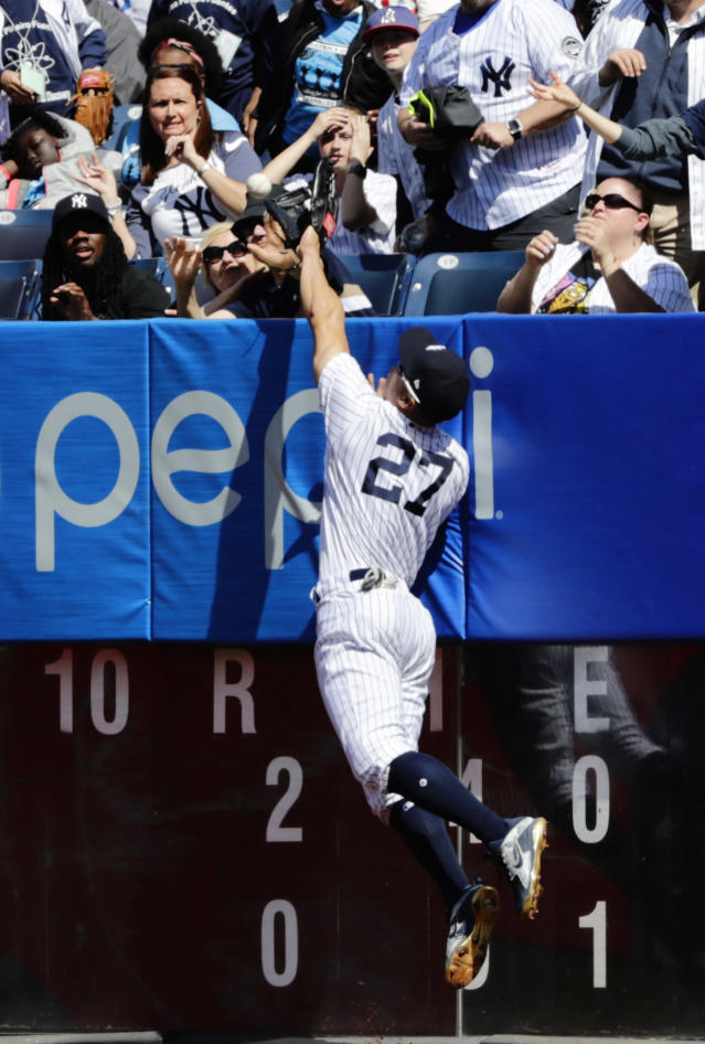Fans react as New York Yankees right fielder Giancarlo Stanton (27) attempts to catch a ball hit by Minnesota Twins' Robbie Grossman for a home run during the sixth inning of a baseball game Thursday, April 26, 2018, in New York. (AP Photo/Frank Franklin II)