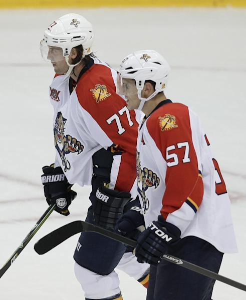 Florida Panthers' Marcel Goc (57) and Tom Gilbert (77) skate back to their bench following Goc's first of two goals scored in the third period of an NHL hockey game against the Dallas Stars, Thursday, Oct. 3, 2013, in Dallas. The Panthers won 4-2. (AP Photo/Tony Gutierrez)