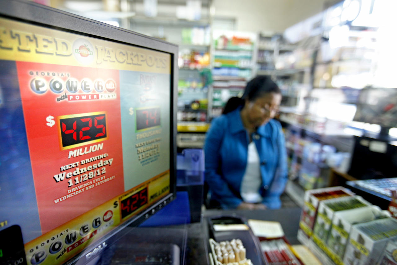 The current Powerball jackpot is seen on a computer screen as Atem Getahun waits for a Georgia lottery machine to print a ticket for a waiting customer at a convenience store, Monday, Nov. 26, 2012, in Atlanta. As the Powerball jackpot soars, a Georgia Lottery official says the agency is working to get its equipment operational again after some machines have been down. Georgia Lottery spokeswoman Kimberly Starks confirmed that some machines were not working properly. She said Monday afternoon that lottery officials are aware of the situation, and are working to correct the problems. (AP Photo/David Goldman)