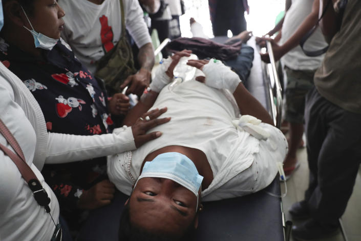 An injured protester is tended to during a demonstration against the military coup in Mandalay, Myanmar, Friday, Feb. 26, 2021. Security forces in Myanmar's largest city on Friday fired warning shots and beat truncheons against their shields while moving to disperse more than 1,000 anti-coup protesters. (AP Photo)